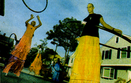 people on stilts with hola hoops
